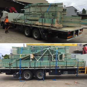 Prefabricated frames on trailer waiting for delivery | Featured image for timber truss & timber frame supplier landing page.